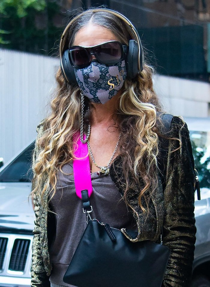Sarah Jessica Parker wears headphones and lace face mask with her initials in gold lettering