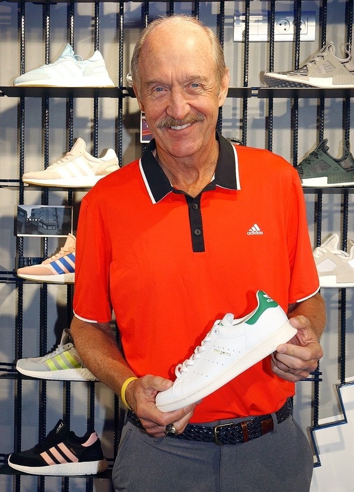 Former world No. 1 American tennis player and two-time Grand Slam singles champion Stan Smith holding a pair of Adidas Stan Smith sneakers