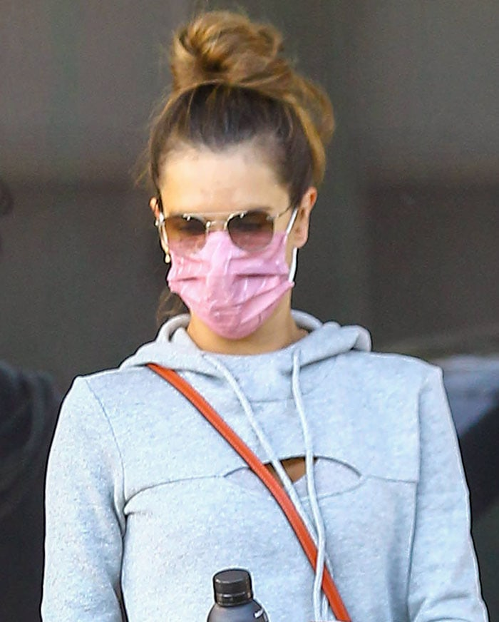 Alessandra Ambrosio wears her hair up in a bun and stays protected with a pink face mask
