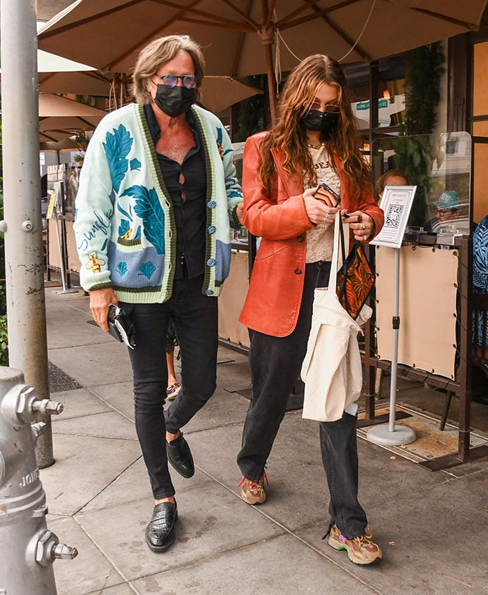 Mohamed Hadid wears a printed cardigan with black shirt and jeans while Bella dons a cream top with black baggy jeans