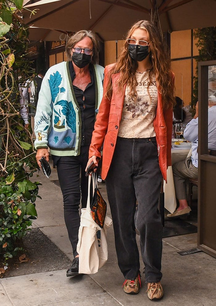 Bella Hadid tops her look with red leather jacket, tinted sunglasses, and black face mask