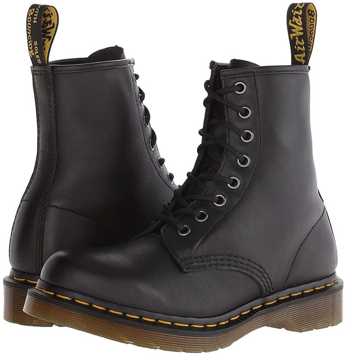 These women's 1460 boots from Dr. Martens feature visible yellow stitching, grooved sides, and a scripted heel-loop