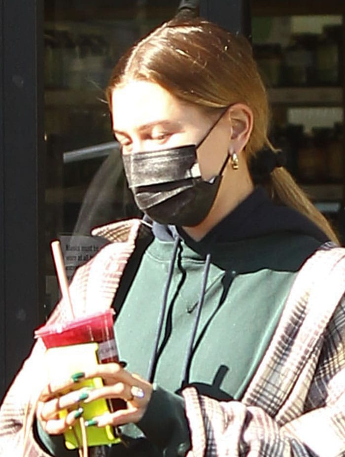 Hailey Bieber wears a bare-faced look with a black face mask for protection against COVID-19