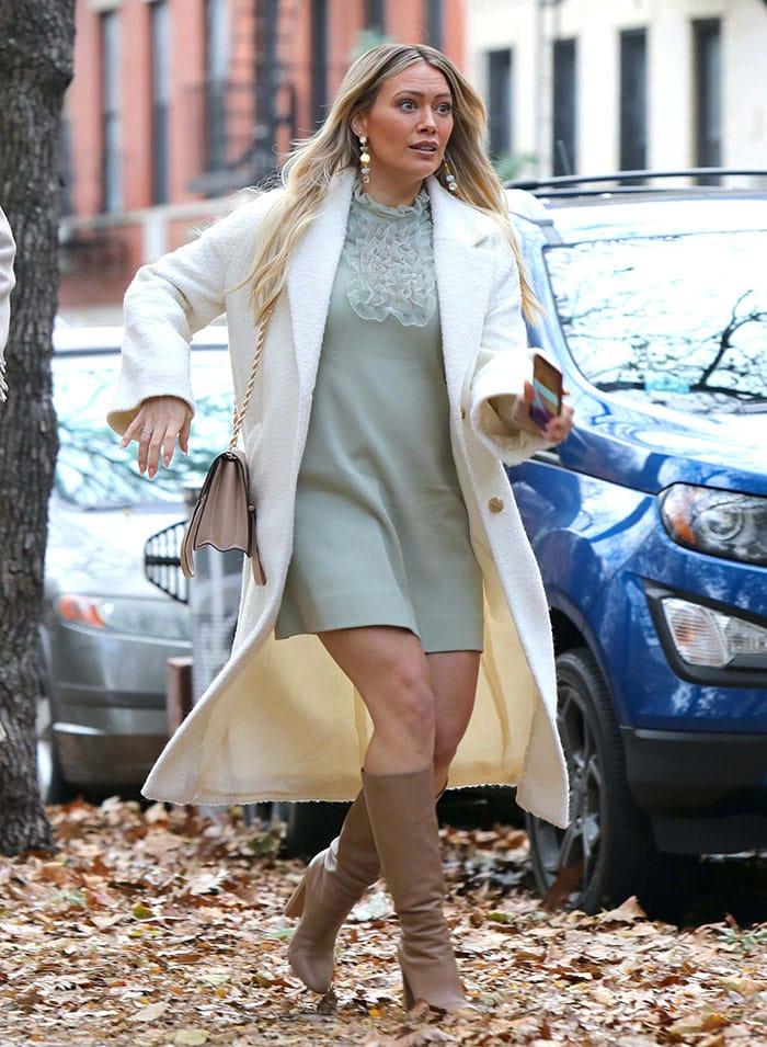 Hilary Duff hides her growing baby bump in a Zara mint green mini dress