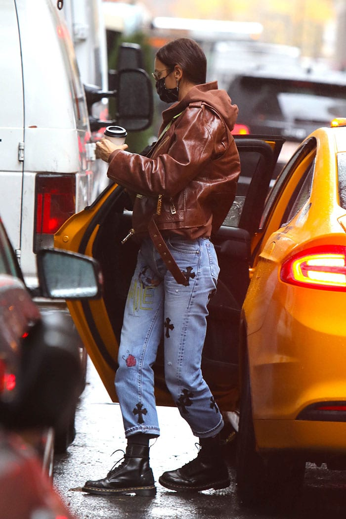 Irina Shayk bundles up in a brown leather jacket with brown hooded sweater and Chrome Hearts jeans