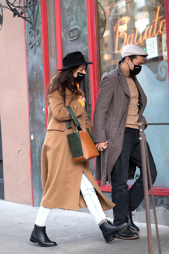 Katie Holmes proves her fall fashion credentials in a Nanushka camel coat with a yellow hoodie and acid-washed jeans