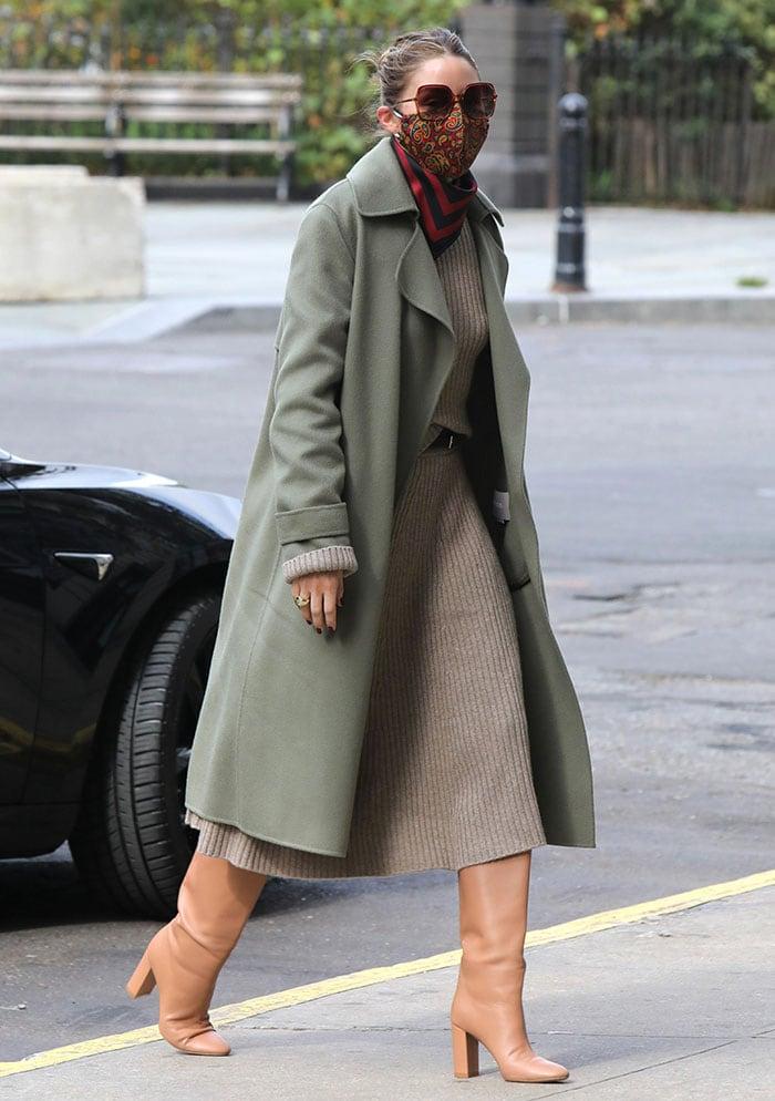 Olivia Palermo wears a gray ribbed knit dress with a khaki green coat