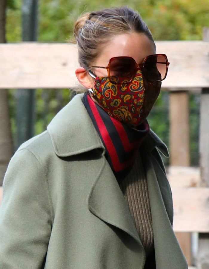 Olivia Palermo keeps it chic with a paisley facemask, rectangular sunglasses, and a red-and-navy scarf