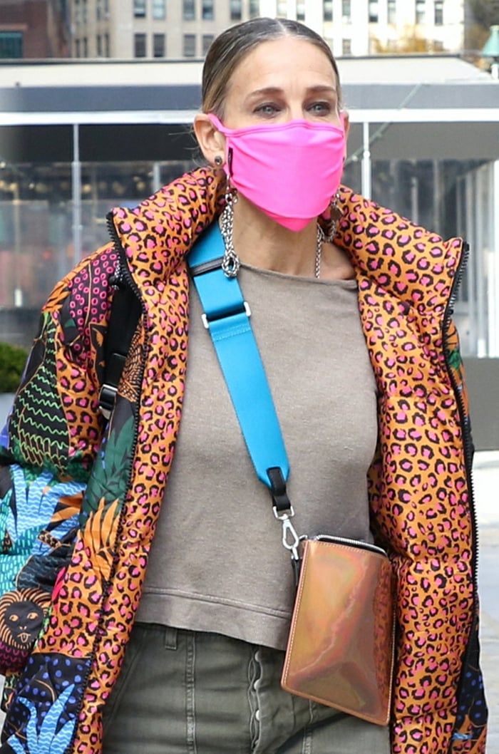 Sarah Jessica Parker pulls her long hair into a ponytail and stays safe with a neon pink face mask