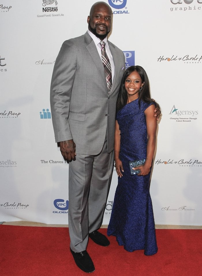 American basketball player Shaquille O'Neal, whose shoes are a size 22, posing with American artistic gymnast Gabby Douglas