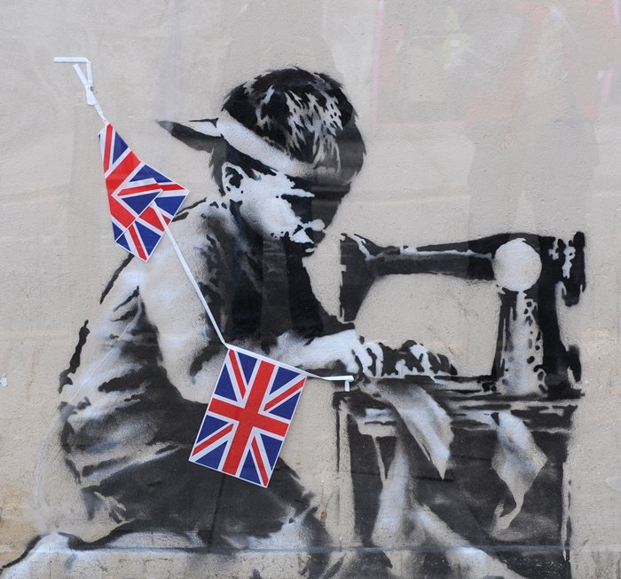 Slave Labour, a mural by British graffiti artist Banksy, depicts a poorly dressed child at a sewing machine assembling a bunting of Union Jack patches