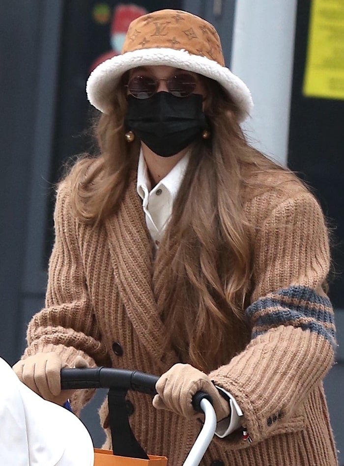 Gigi Hadid goes monochromatic as she pairs her quilted coat with a beige Louis Vuitton shearling-lined bucket hat