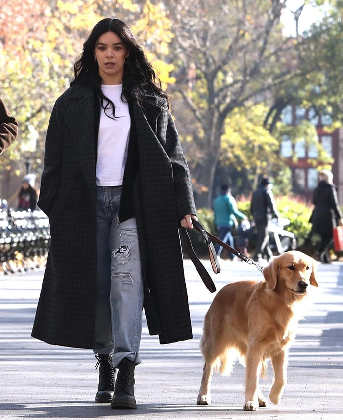 Hailee Steinfeld wears a white tee with ripped jeans and a plaid wool coat