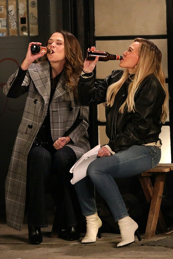 Hilary Duff filming a scene with Sutton Foster in black leather jacket and white heeled boots on December 11, 2020