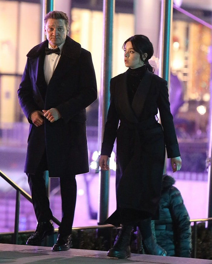 Jeremy Renner in a tuxedo and Hailee Steinfeld in a trench coat on the Hawkeye set