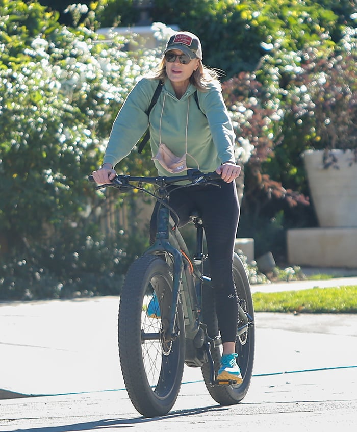 Robin Wright wears a green hoodie with black leggings for the afternoon bike ride