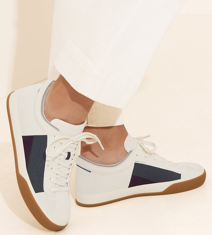 Designed for supportive structure and cloud-like comfort, this cream sneaker features dark blue-grey and purple color blocking on both sides of the shoe