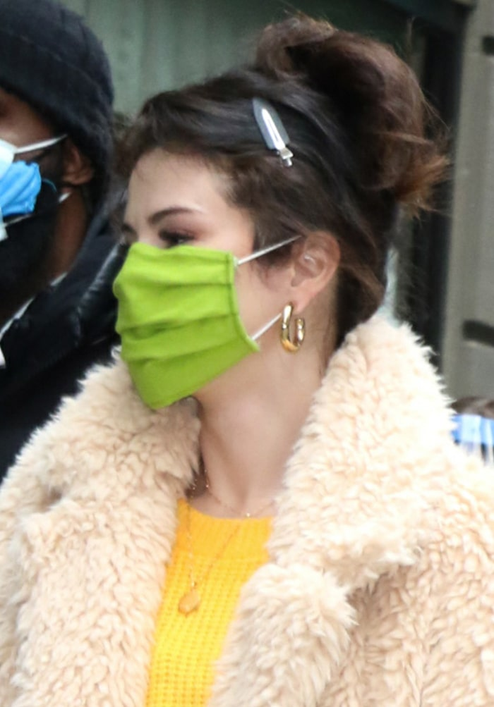 Selena Gomez wears her hair in a messy bun and stays safe with a green face mask