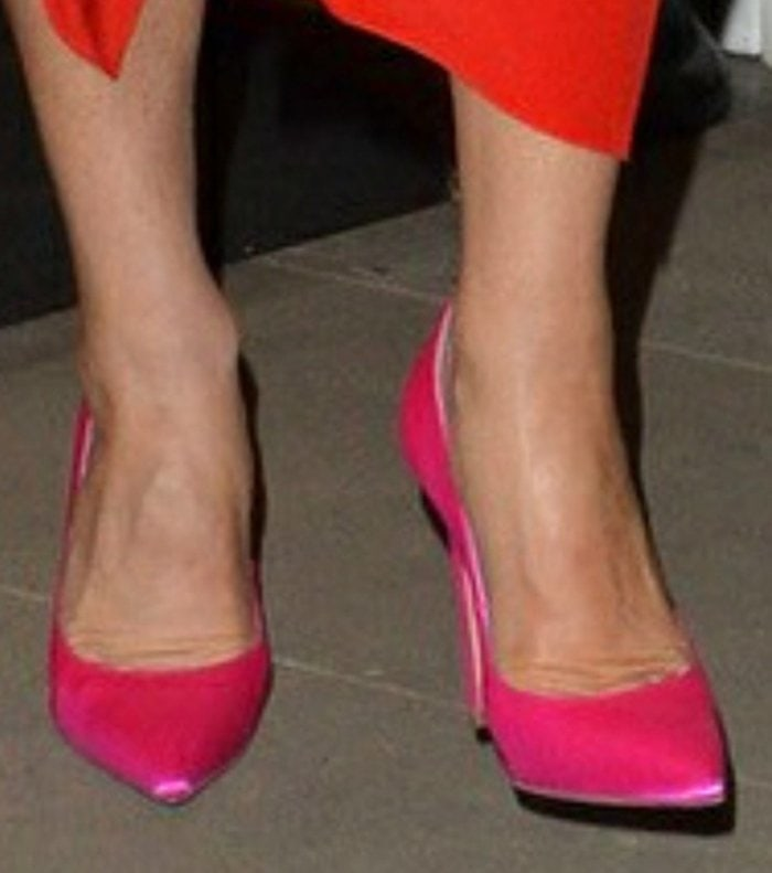 Victoria Beckham teams her red dress with a pair of hot pink VB 90 pumps
