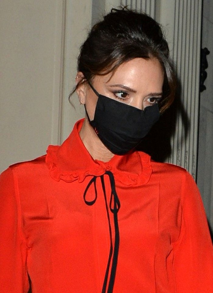 Victoria Beckham styles her hair up in a chignon and stays protected with a black face mask