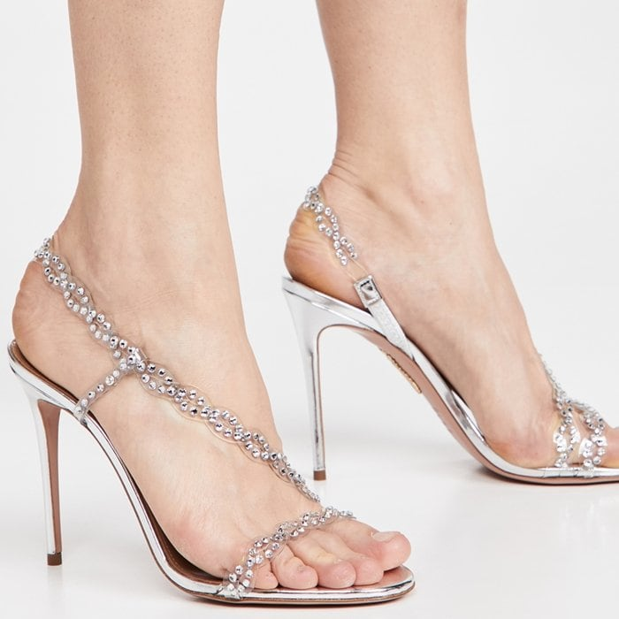 Made of shimmery silver mirrored leather, this open-toe sandal features glamorous gems on its PVC straps that wrap across the toe and around the ankle