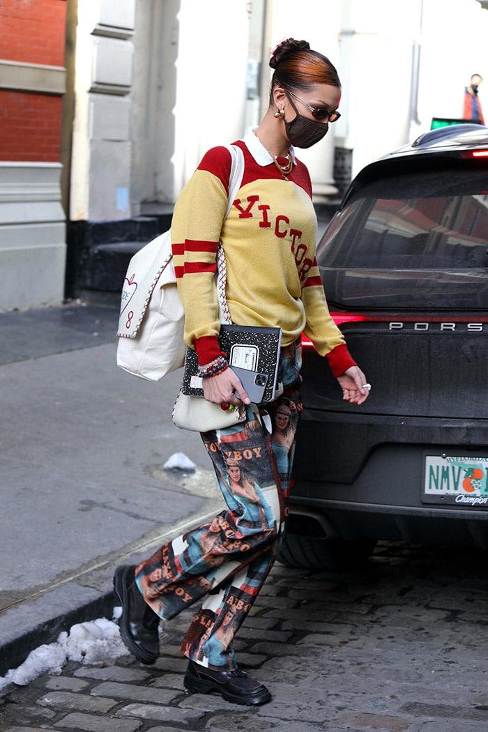 Bella Hadid teams her pullover with Soulland Playboy motif baggy corduroy pants