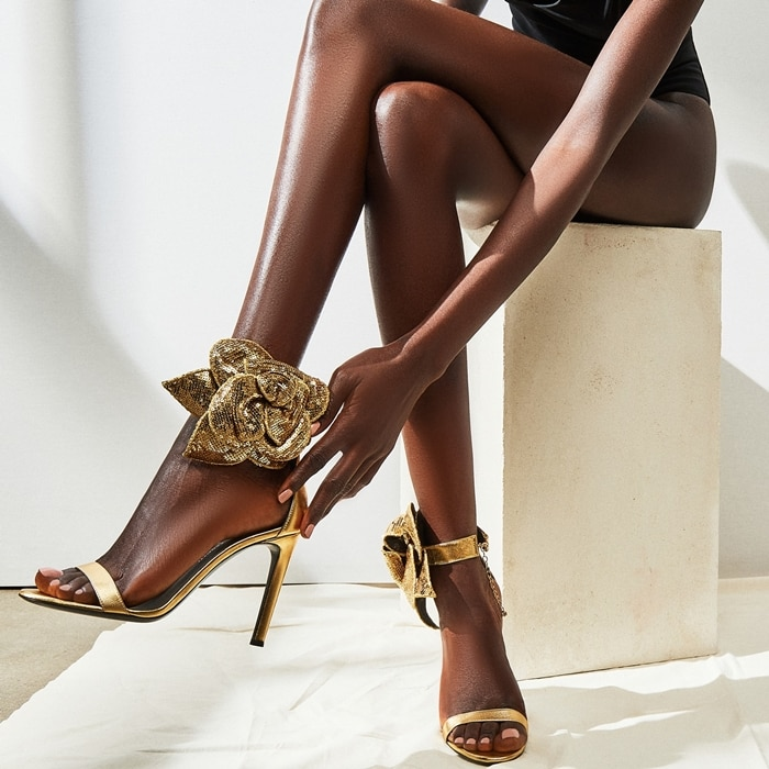 These high-heel, laminated golden leather sandals feature a single front strap and are characterized by the handmade, golden sequin 'Rose' accessory on the side