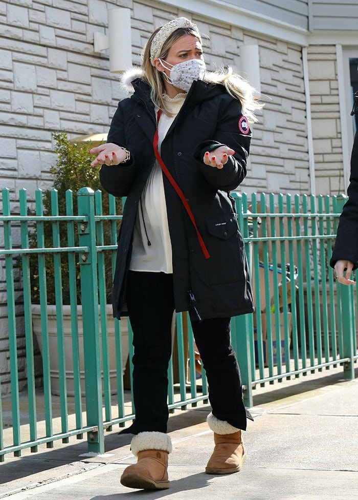 Hilary Duff changes into a cream-colored blouse, Canada Goose parka, and comfier UGG boots