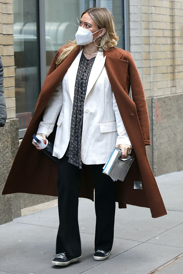 Hilary Duff trades her animal-print outfit for a white blazer with a printed blouse underneath