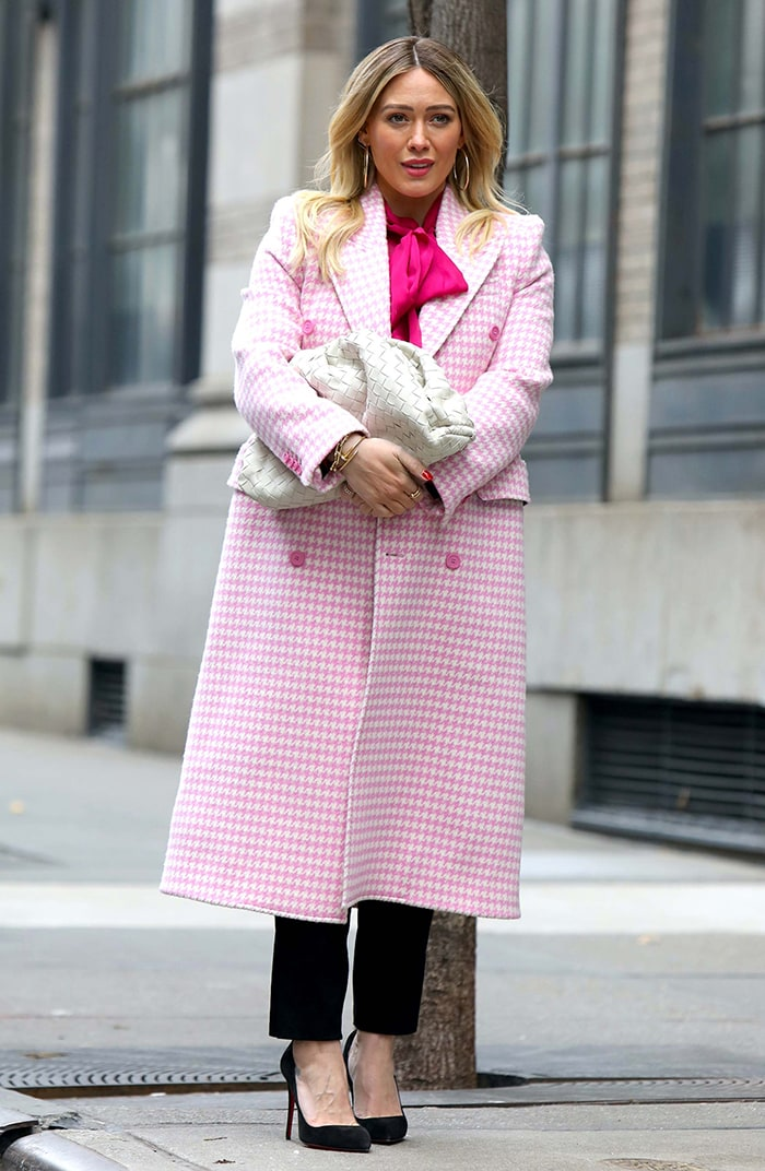 Hilary Duff in a light pink Hourglass coat from Balenciaga channels Elle Woods while filming Younger