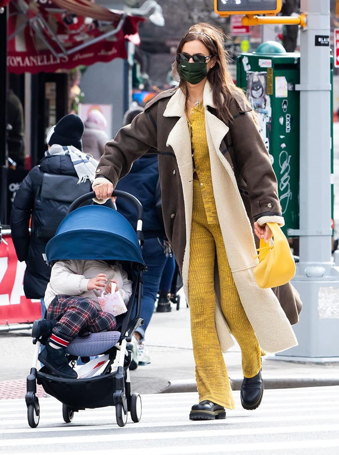 Irina Shayk pairs her coat with a loungewear-inspired Live the Process yellow cardigan and flare pants