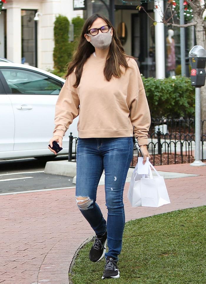 Jennifer Garner wears a beige Tkees sweater with blue ripped jeans