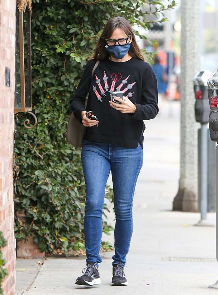 Jennifer Garner teams her Brooks shoes with blue jeans and black Valentino sweater on December 17, 2020