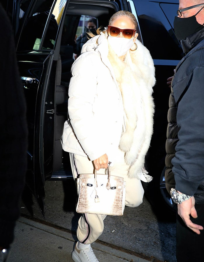 Jennifer Lopez bundles up in Olivia Von Halle Missy Moscow track suit, Wilfred Cloud Puff jacket, and a furry scarf