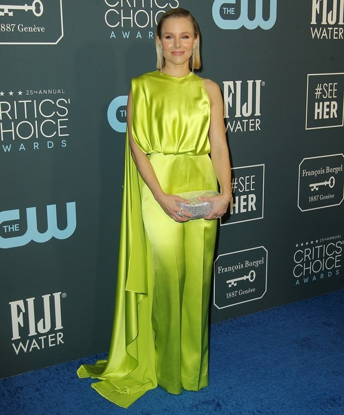 Kristen Bell wears a silky neon Cong Tri jumpsuit, Forevermark jewelry, a Christian Louboutin clutch, and Brian Atwood heels at the 2020 Critics' Choice Awards