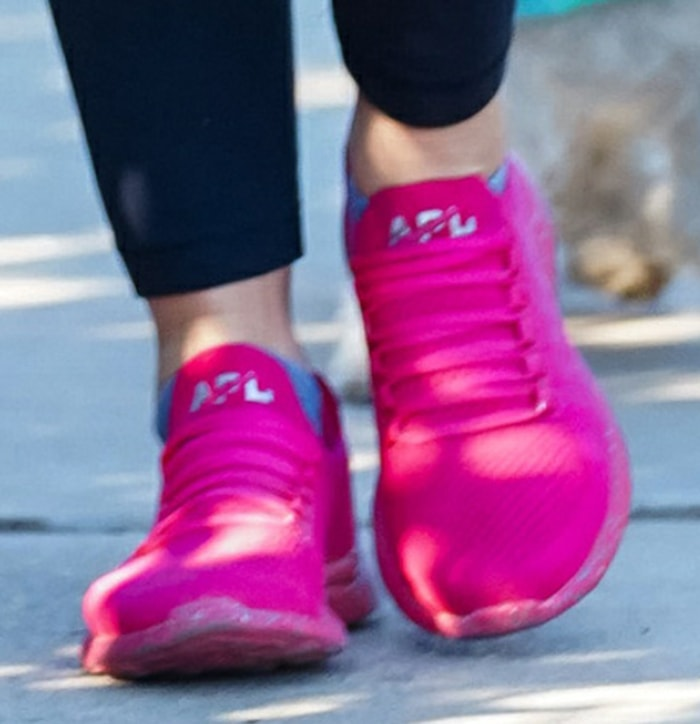 Lucy Hale adds color to her dark-themed hiking look with APL hot pink sneakers