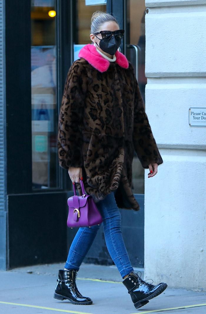 Olivia Palermo teams a pink fur-trimmed leopard-print coat with slim-fit blue jeans