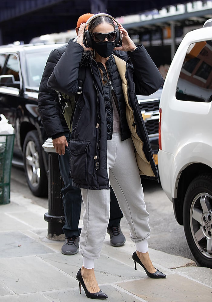 Sarah Jessica Parker bundles up in two layers of outerwear outside her shoe store