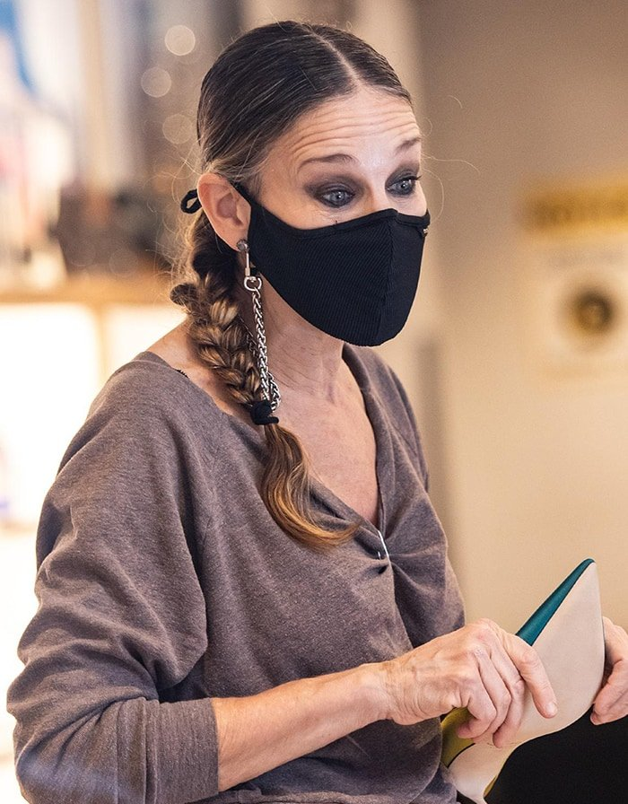 Sarah Jessica Parker adheres to CDC safety protocols by wearing a ribbed face mask with a chain strap