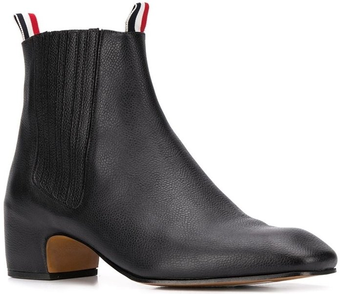 Boasting the iconic three-stripe detailing and a unique block heel, these black calf leather Thom Browne Chelsea boots are distinctive in their design and add a little bit of height to your ensemble