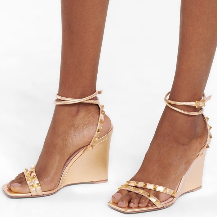 These Rockstud wedges from Valentino Garavani are made from lamb leather in a metallic golden hue and are defined with tonal pyramid embellishments