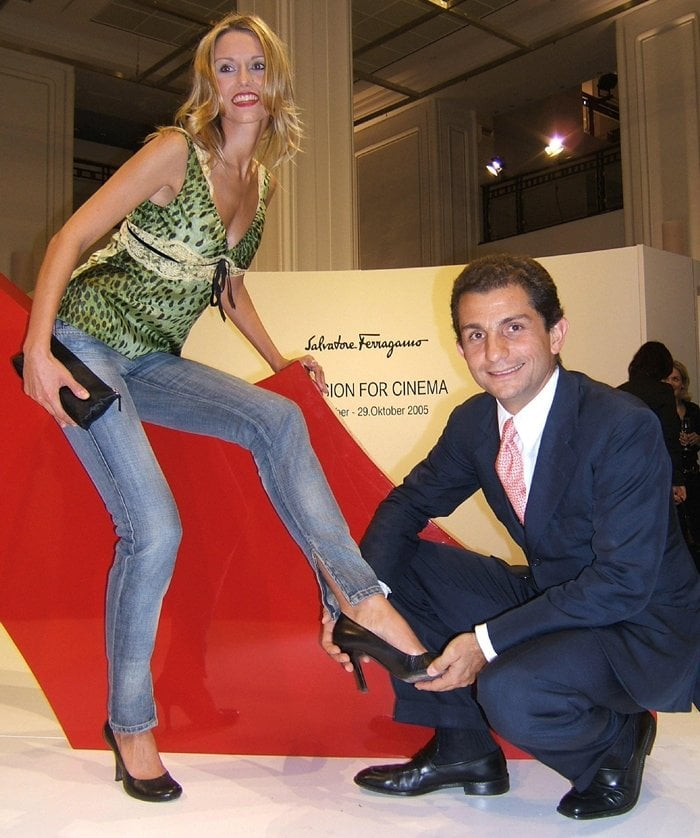 Jewelry designer Yvonne Hoelzel gets help from Diego Paterno Castello di San Giuliano to try on a pair of Salvatore Ferragamo shoes