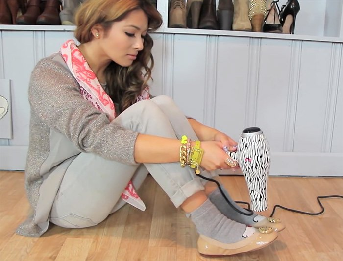 A screenshot from Lisa Pullano's YouTube channel showing how to stretch and break in shoes using thick socks and a blow dryer