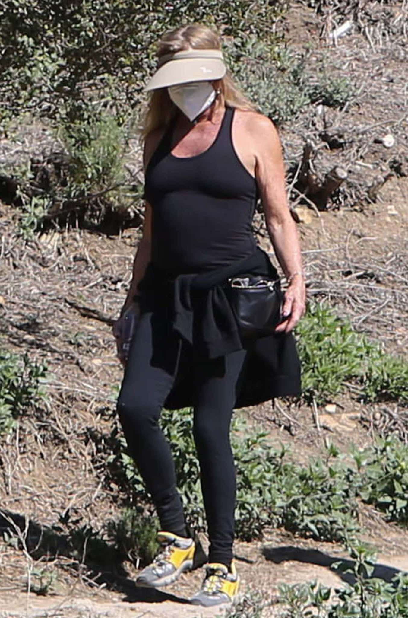 Goldie Hawn wears a tank top with leggings and gray-and-yellow shoes during a hiking excursion