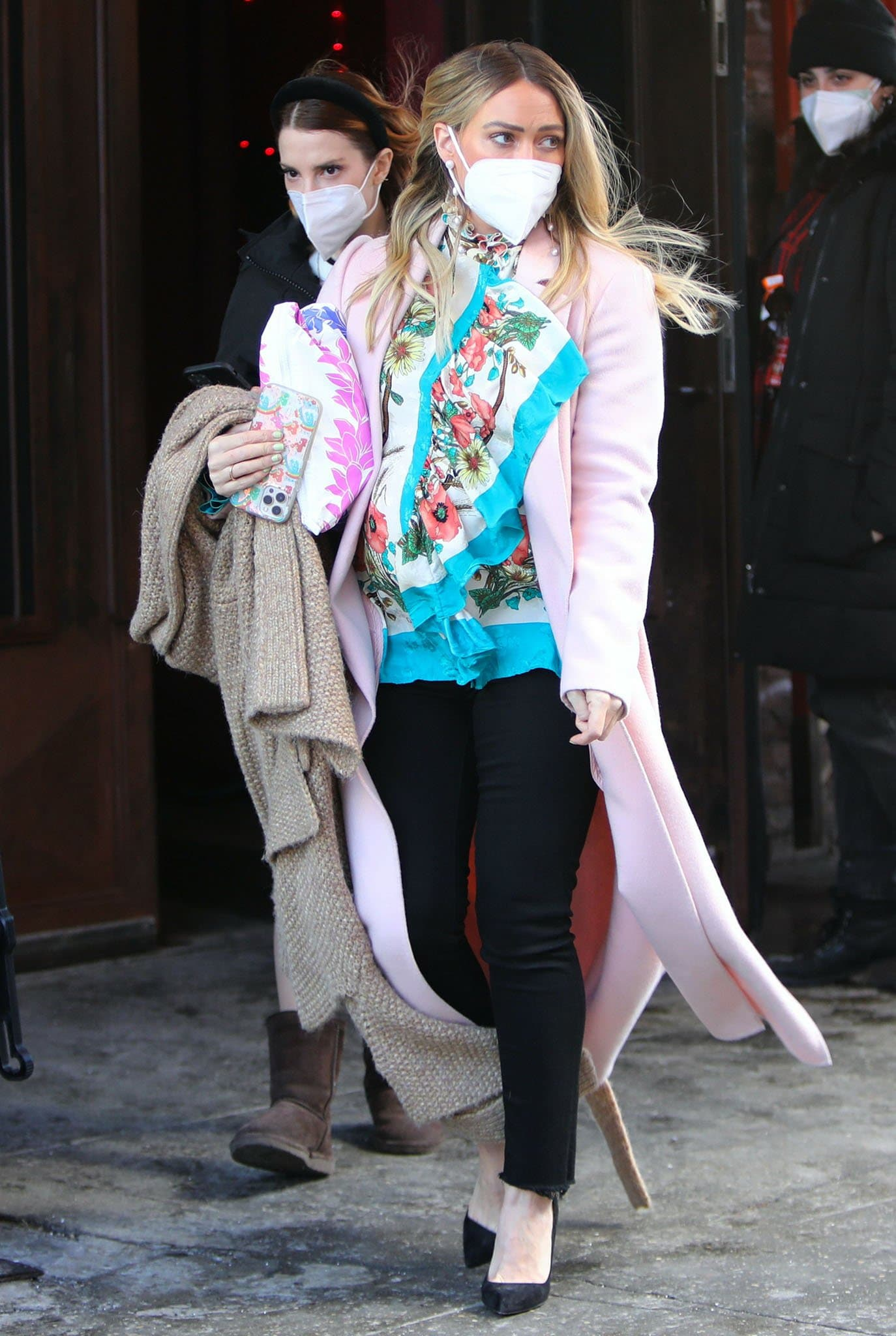Hilary Duff pairs her ruffled blouse and coat with black pants and suede pumps