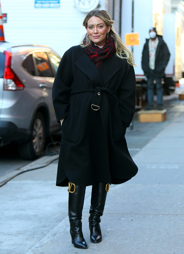 Hilary Duff covers her baby bump in a black trench coat and red-and-black printed scarf