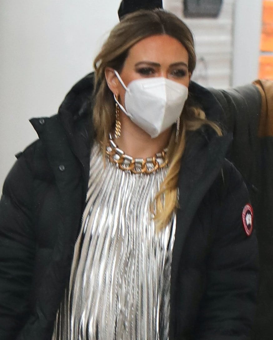 Hilary Duff accessorizes with long chain earrings and stays safe with a face mask