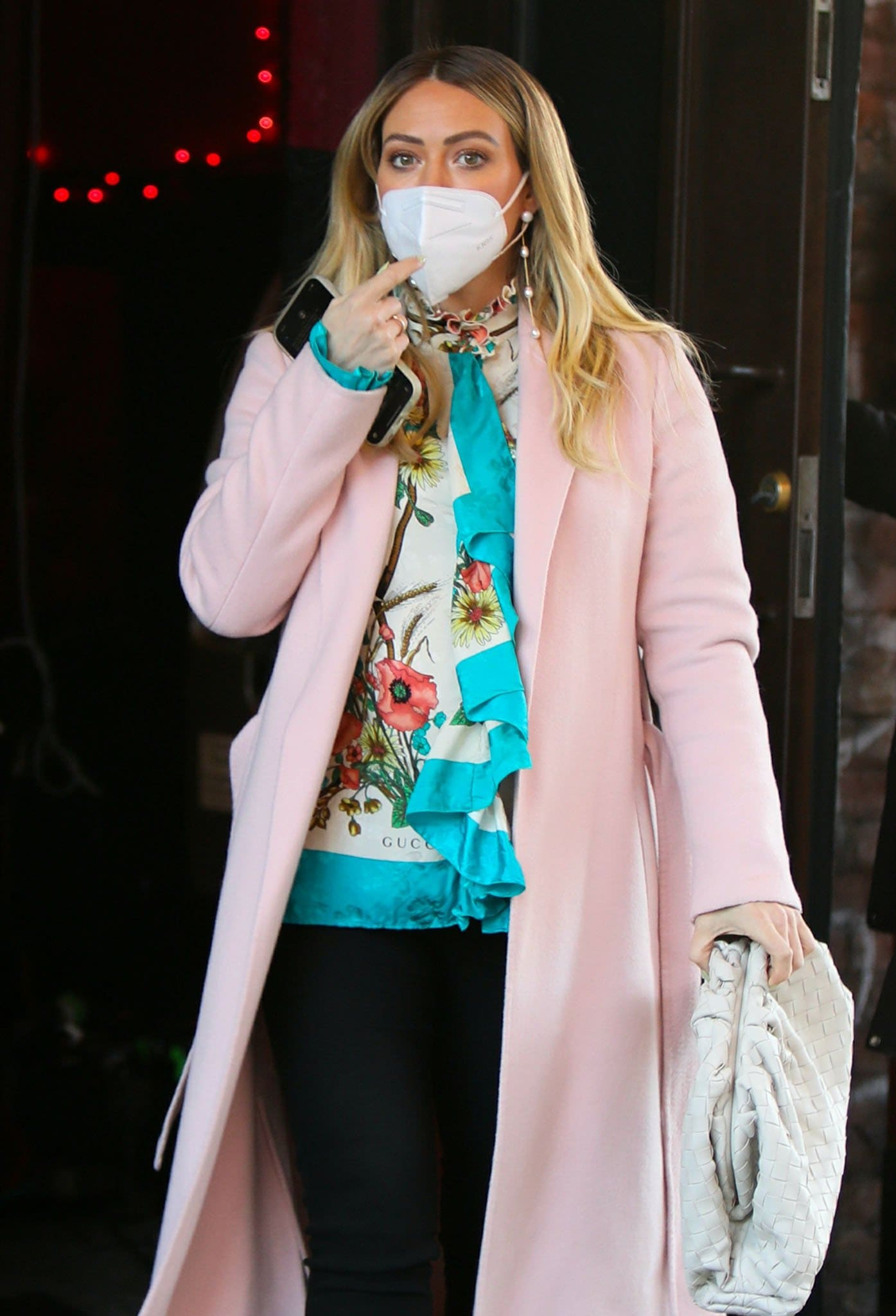 Hilary Duff styled her girly look with long pearl earrings and Bottega Veneta pouch