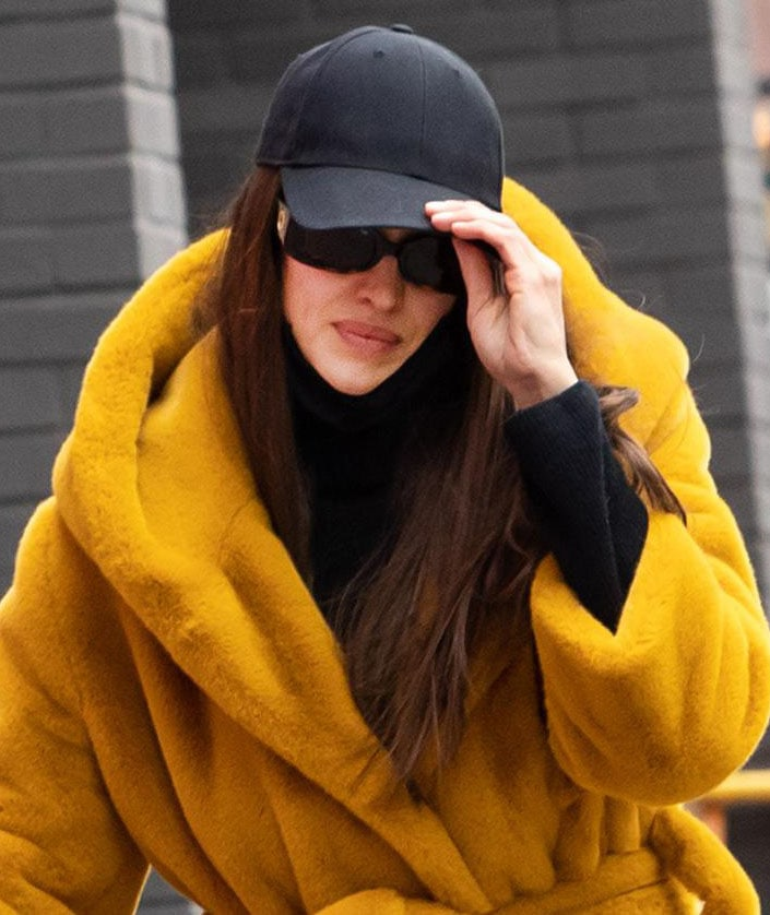 Irina Shayk keeps the rest of her look low-key with a black cap and Linda Farrow sunglasses