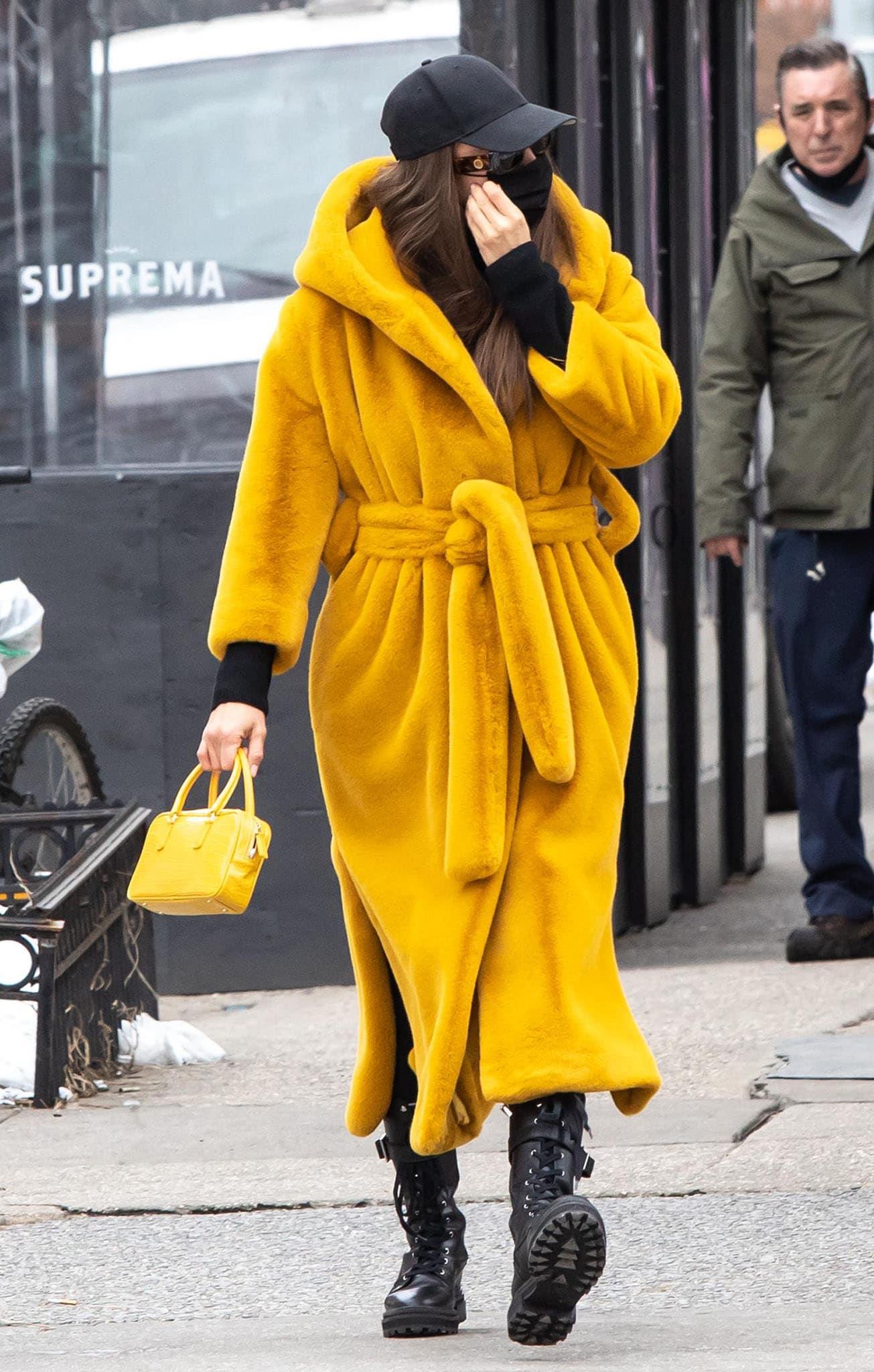 Irina Shayk wears Olēnich faux-fur yellow wrap-style coat with black Intimissimi cashmere leggings
